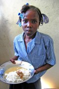 A child with a plate of food in Jamaica