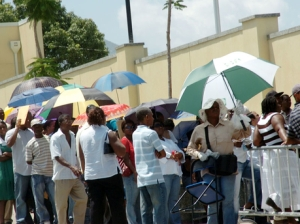 Jamaicans wait in line at the US Embassy in Kingston, and a 'Nadine' is on hand to hold valuables