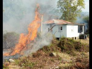 A bush fire threatens this house in Llandewey, western St. Thomas. This photo was taken in May, 2015. (Photo: Ian Allen/Gleaner)